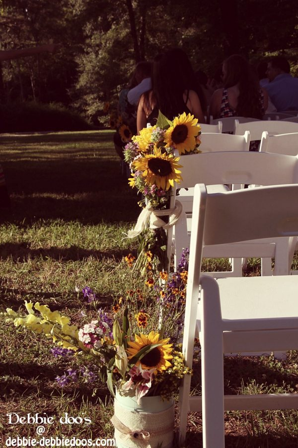 Wedding set up with flowers tied to the end of chairs
