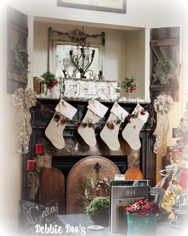 Christmas mantel with burlap stockings, rustic gardland and marquee lighting and faux greenery wreaths