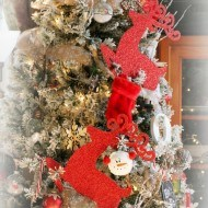 Flocked Christmas tree adorned in reds and traditional ornaments