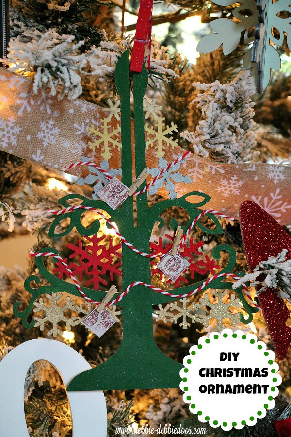 diy christmas wood ornament with craft paint, mod podge, scrap book paper and mini clothes pins and bakers twine
