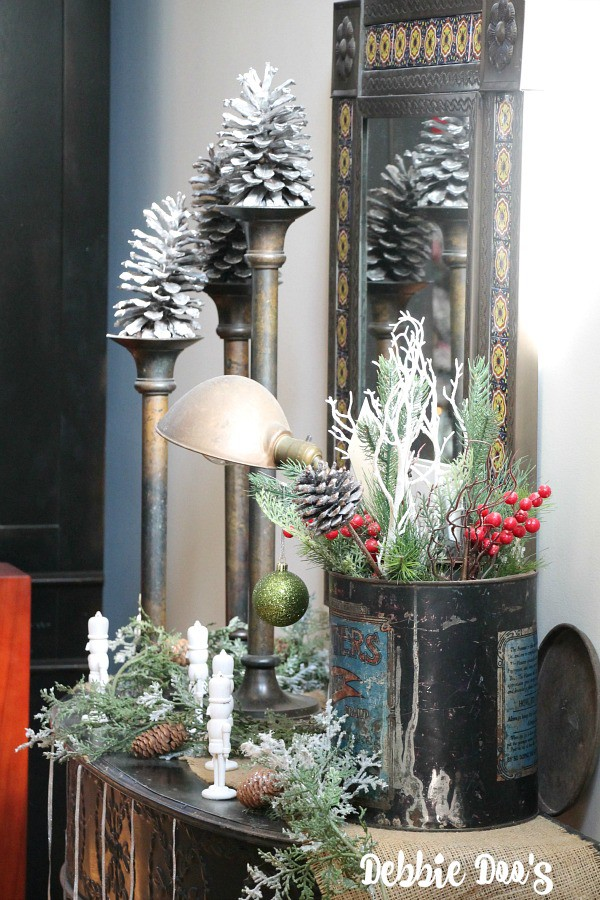 large pinecones on side table and Christmas vignettes with vintage decor