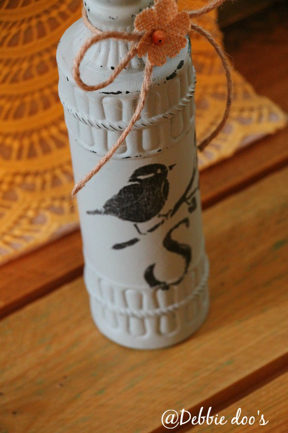 Stenciled bird and monogram on a bottle