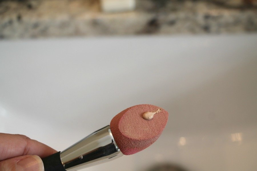 Applying foundation with a sponge applicator brush