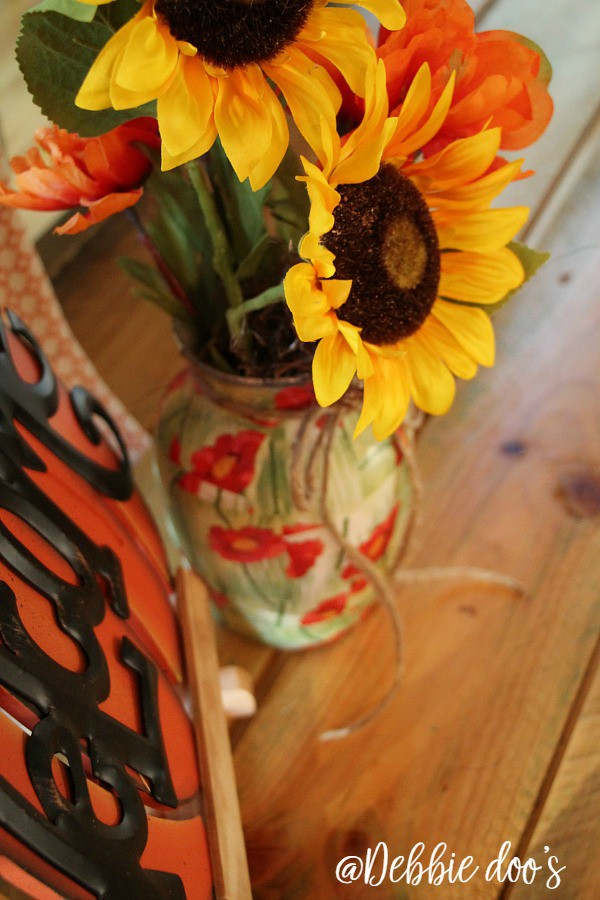 Faux sunflowers in a poppy vase