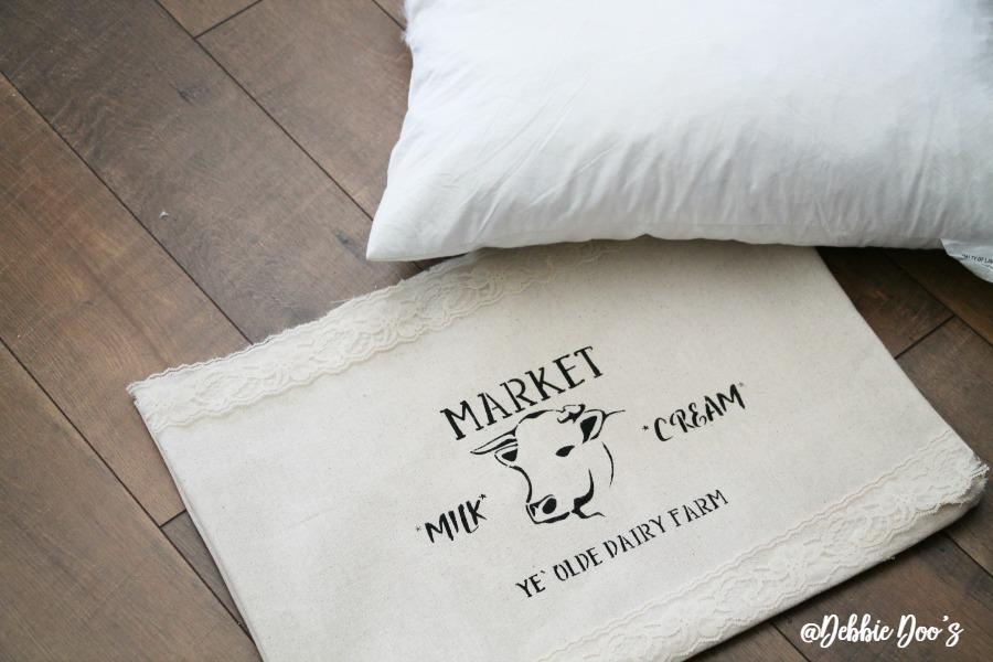 no-sew-drop-cloth-pillow-by-debbiedoos-with-market-cow-stencil